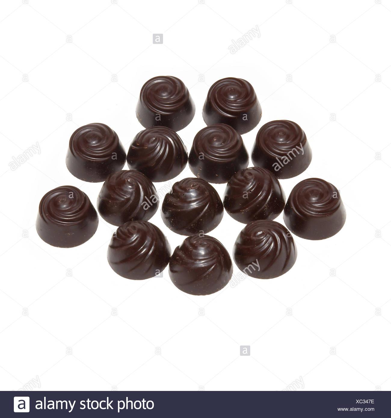 Delicious dark chocolate pralines isolated on white. - Stock Image