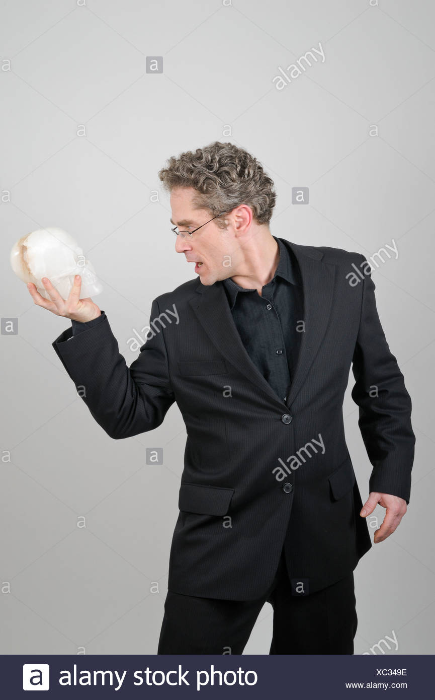 Businessman wearing a black suit holding a white skull made of alabaster in his hand, To Be or Not to Be, Shakespeare's Hamlet - Stock Image