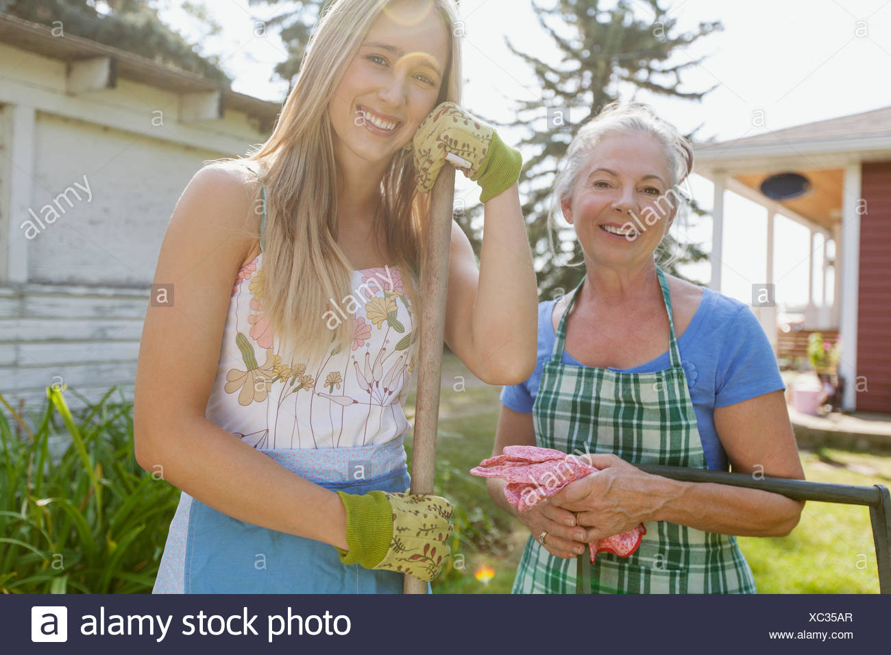 Mother and daughter outdoors doing yard work. - Stock Image