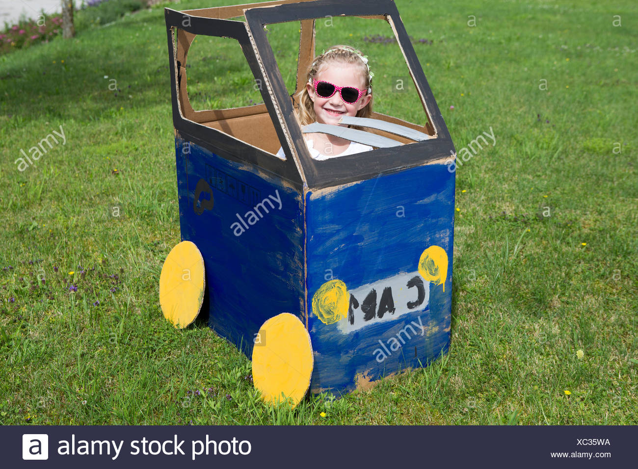 Girl playing in homemade toy car - Stock Image
