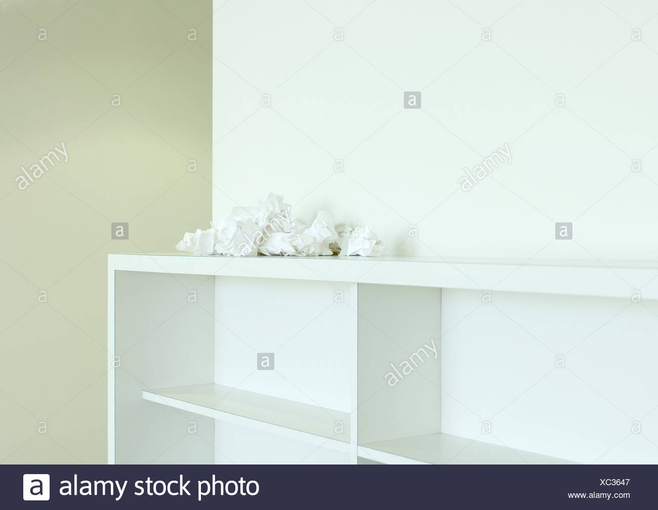 Crumpled papers on top of empty bookcase - Stock Image
