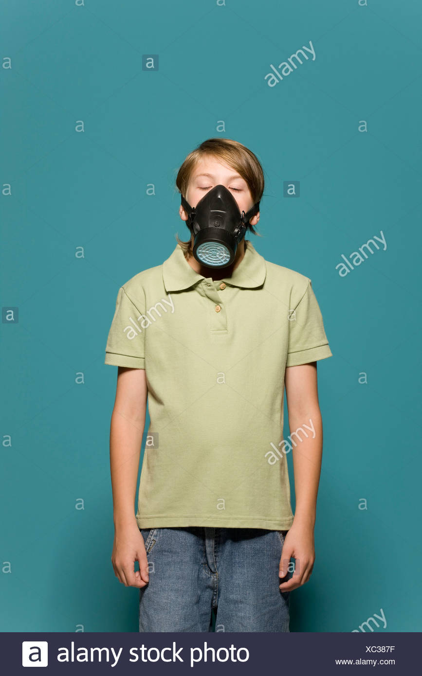 Boy wearing gas mask, eyes closed - Stock Image