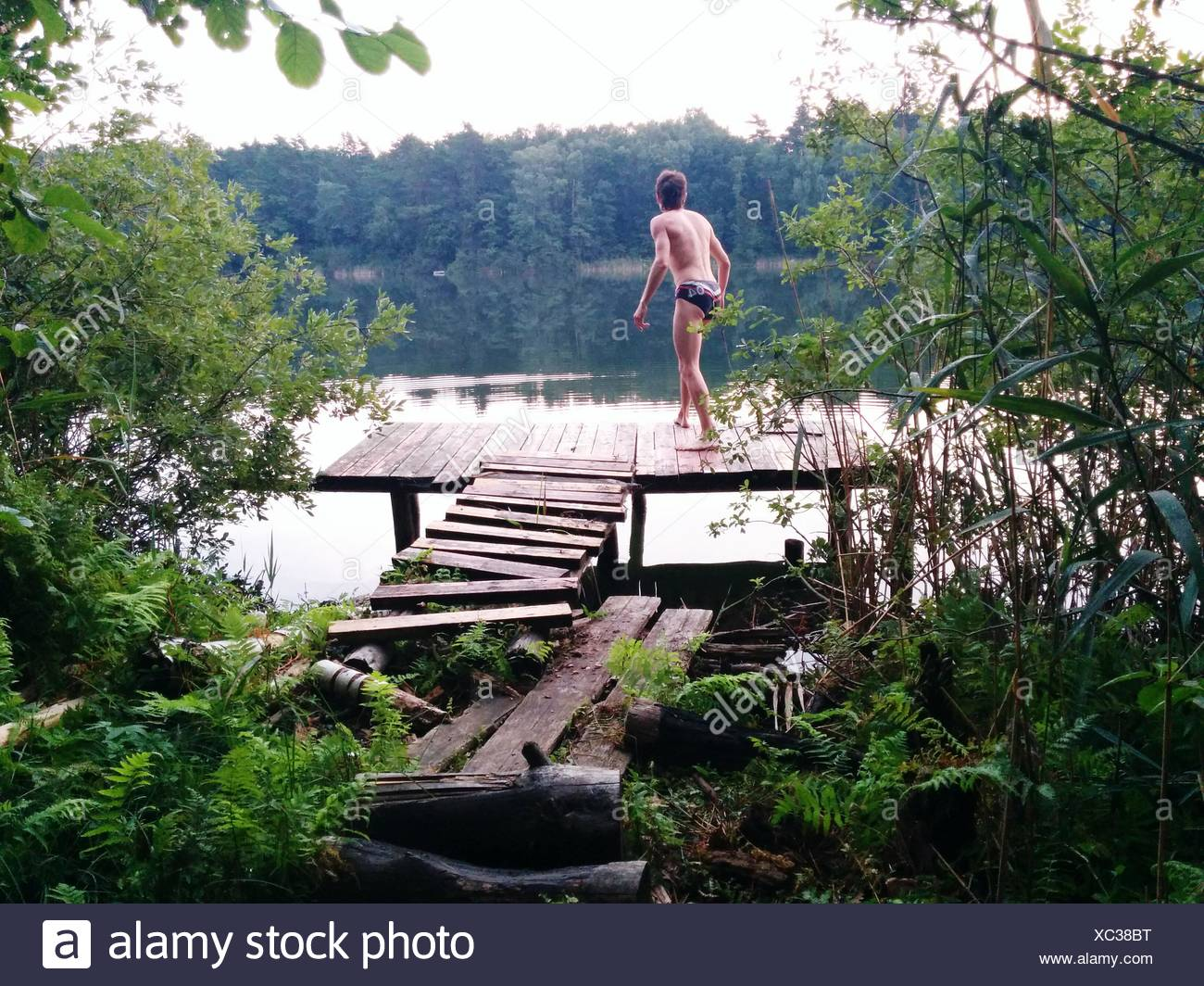 Rear View Of Man Standing At Lakeshore - Stock Image