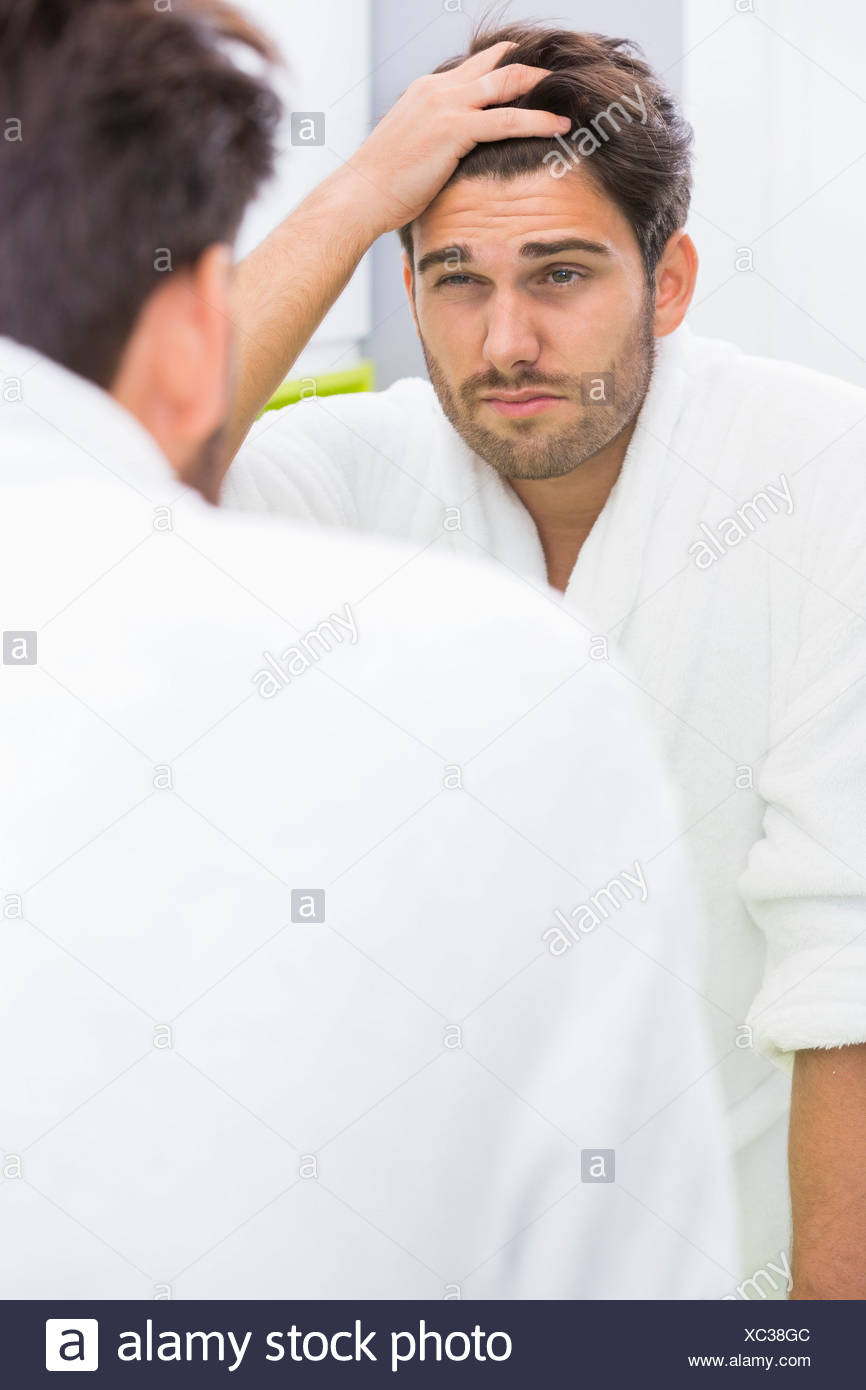 Reflection of man suffering from headache in mirror - Stock Image
