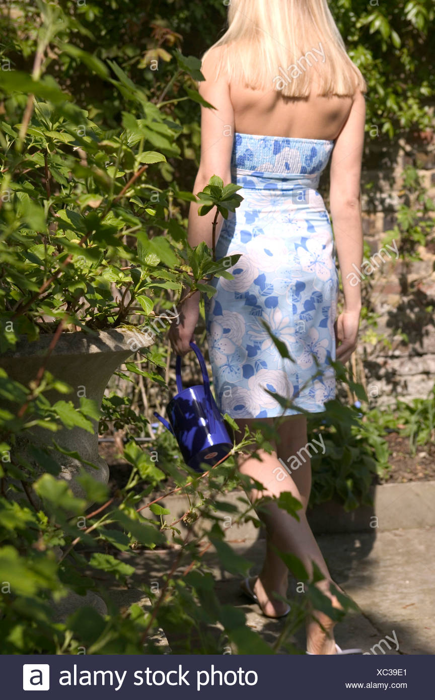 072be93bc29d9 Back view of female long blonde hair wearing knee length strapless blue and  white floral dress