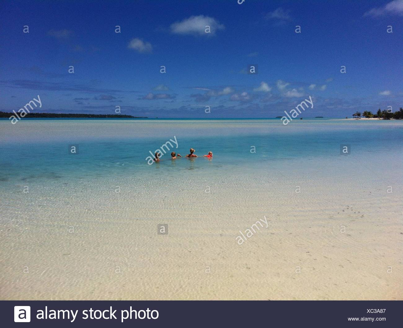 Mother and three children swimming in sea - Stock Image