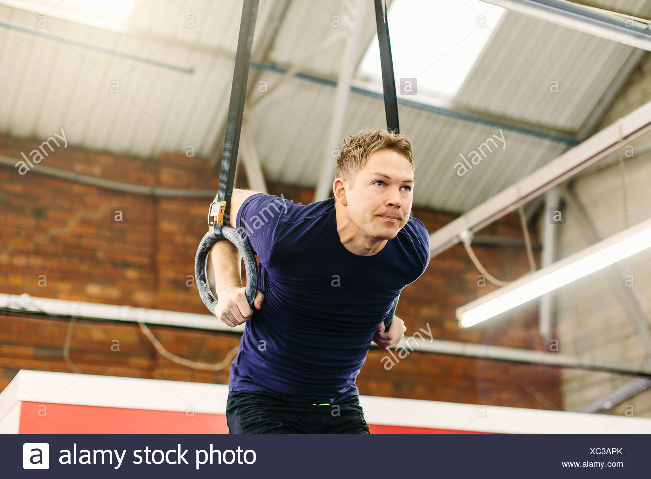 Man pulling suspended rings in gym - Stock Image