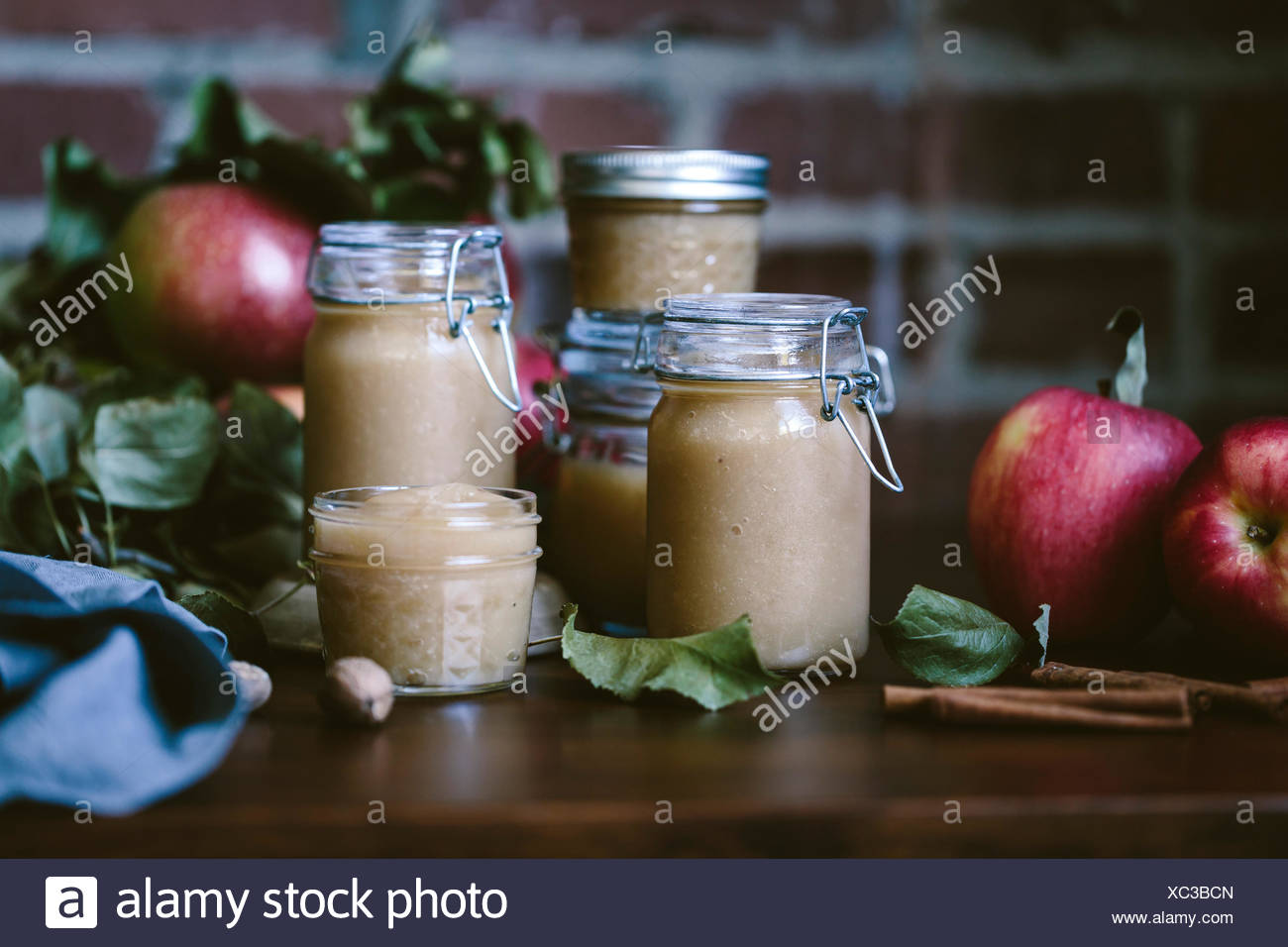 Glass jars filled with homemade slow cooker applesauce are photographed from the front view. - Stock Image