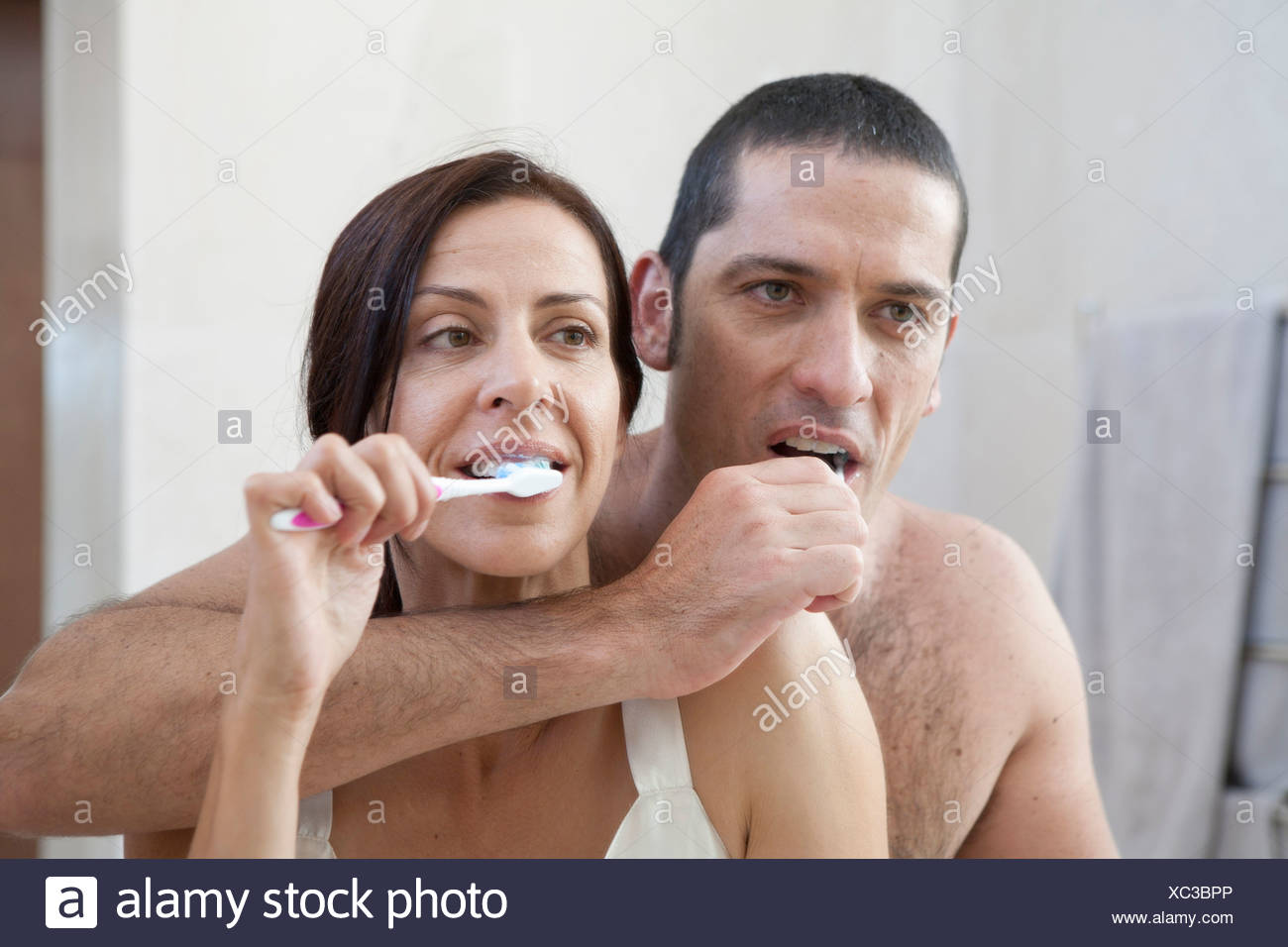 Couple brushing their teeth in bathroom - Stock Image