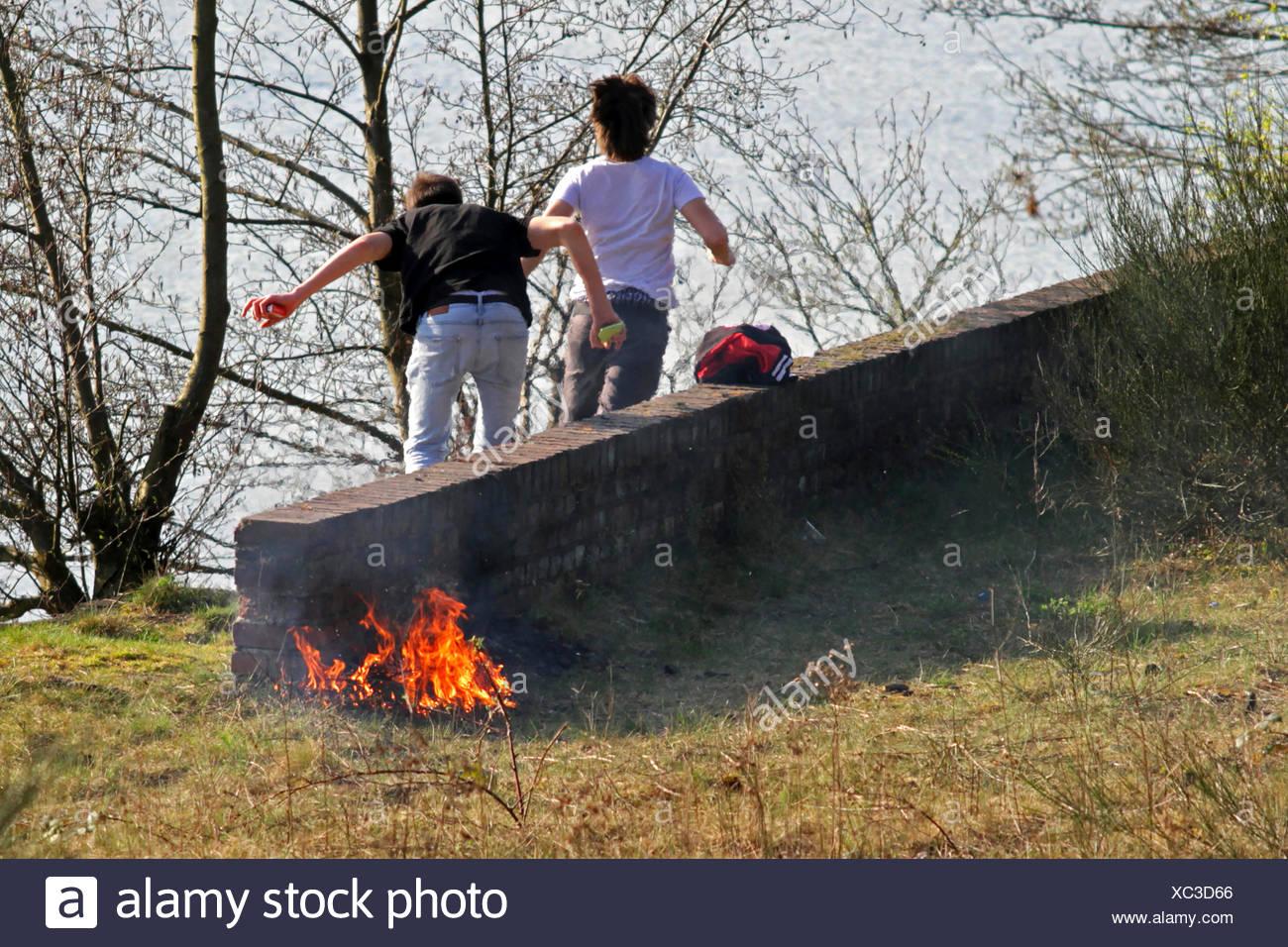 Jugendliche entfachen ein Feuer und ergreifen die Flucht, um sich einer Bestrafung zu entziehen, Deutschland | teens fanning the Stock Photo