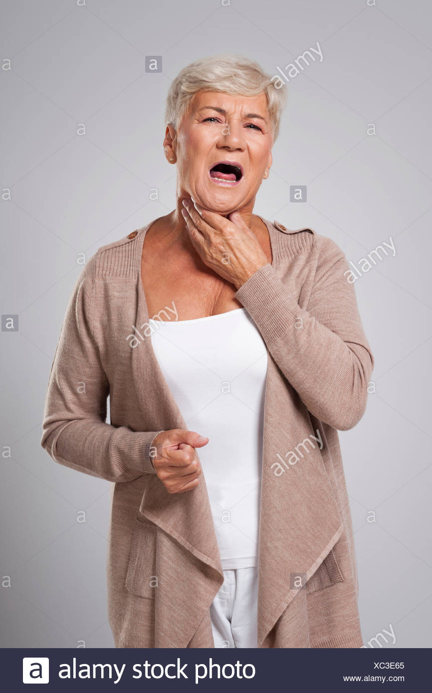 Older lady with a sore throat - Stock Image