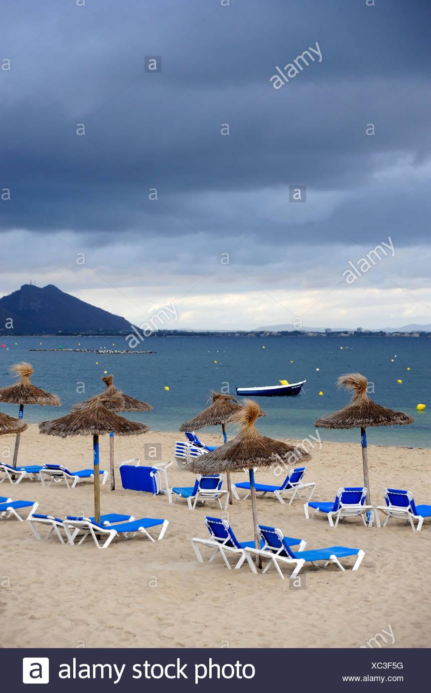 Sunbeds and parasols on a beach, overcast sky, Puerto de Pollensa, Port de Pollenca, Mallorca, Majorca, Balearic Islands Stock Photo
