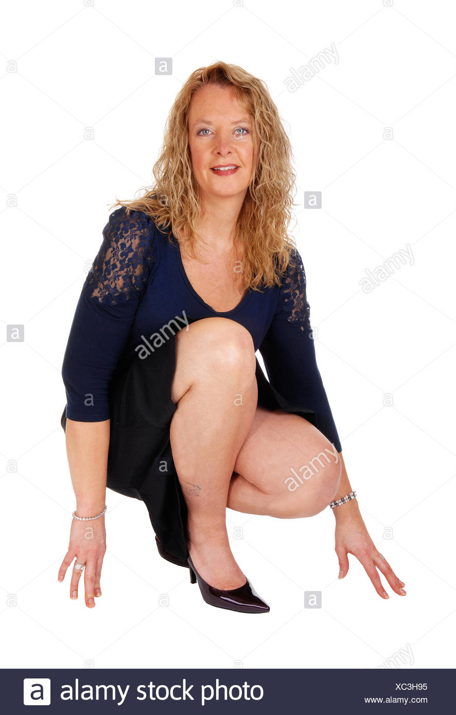 Lovely woman crouching on floor. Stock Photo