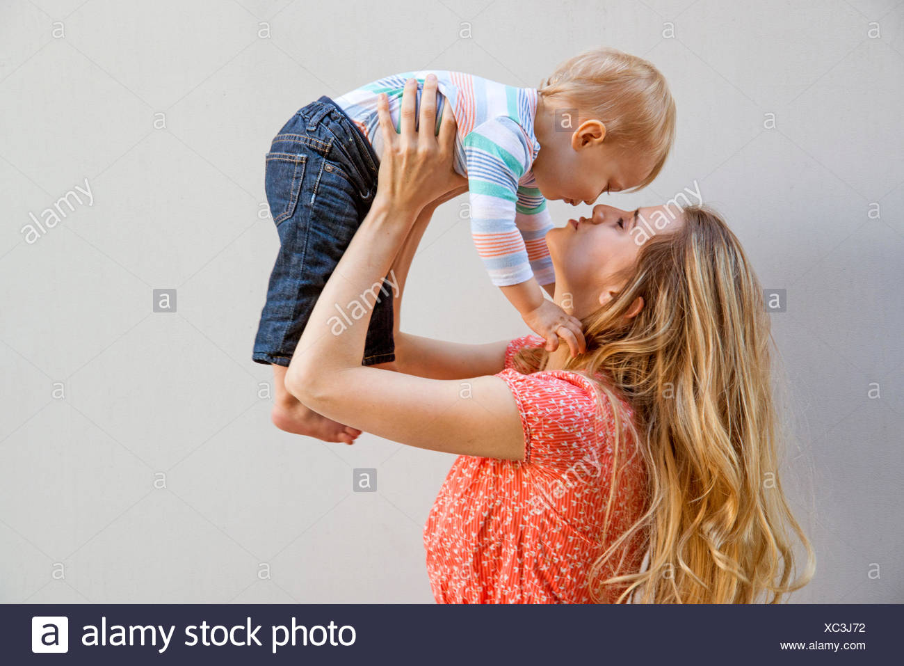 Mother holding her son (12-17 months) face to face - Stock Image