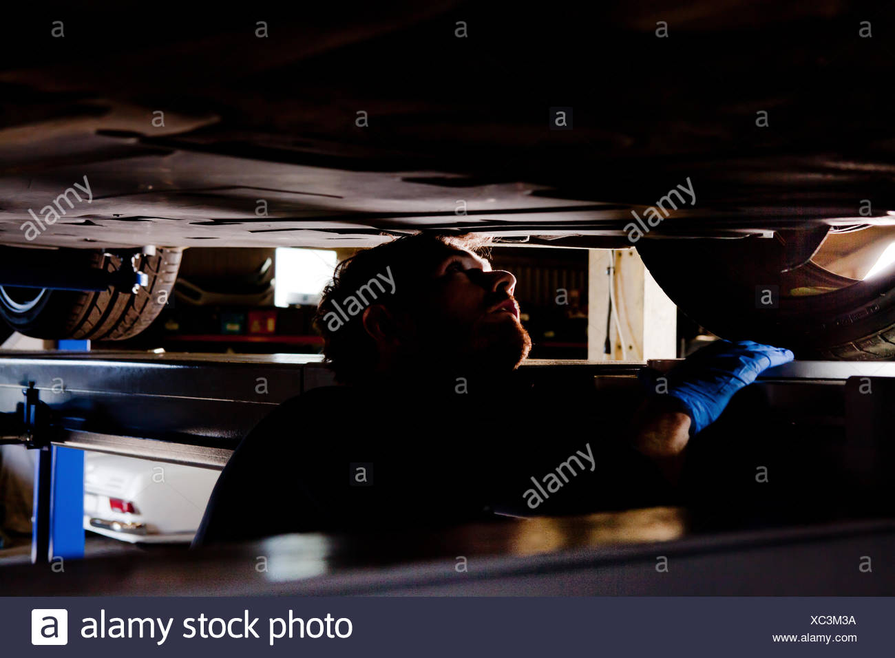 Male mechanic underneath car, looking for problem - Stock Image
