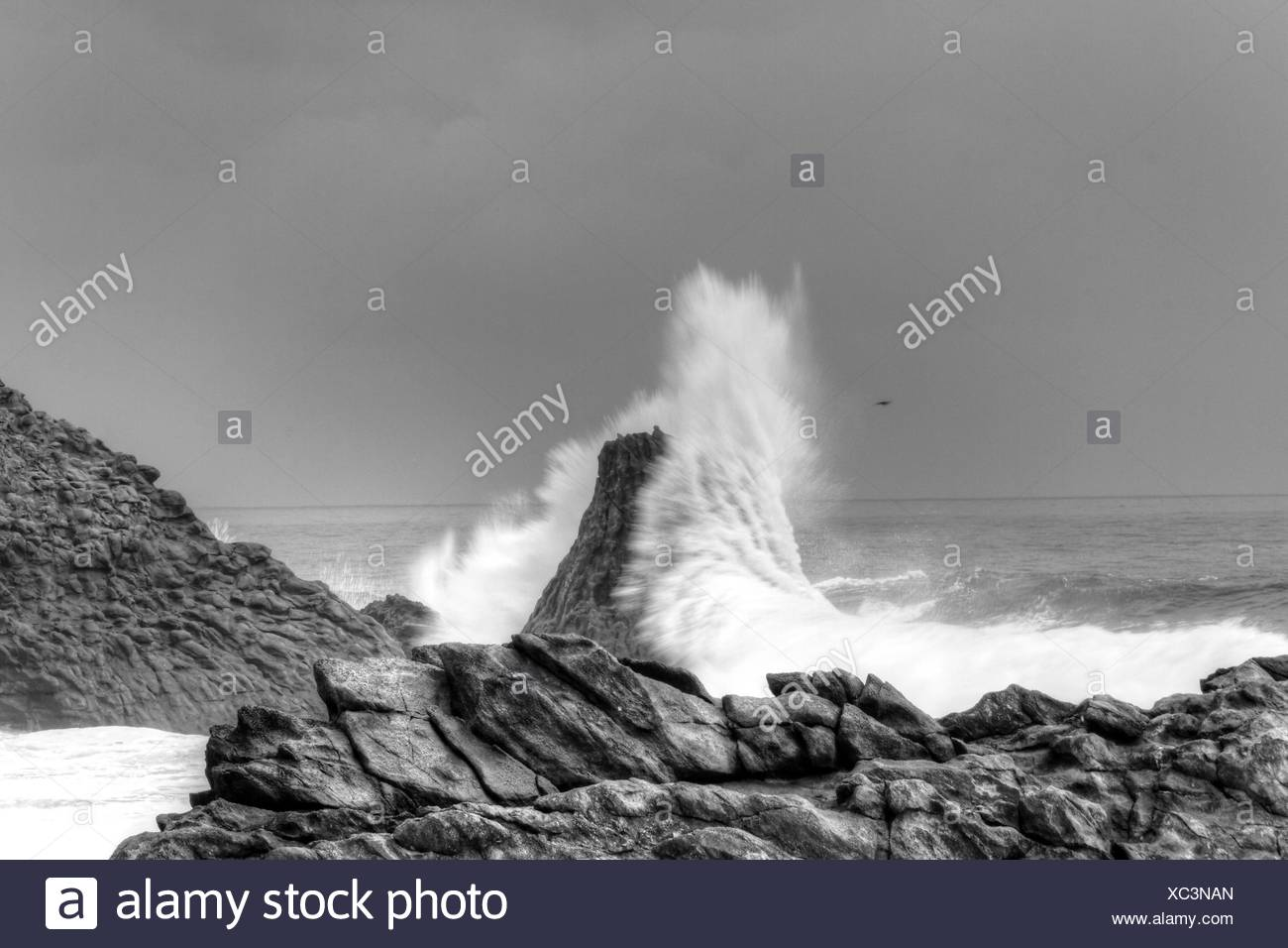Waves Breaking On Rocks At Overcast Day - Stock Image