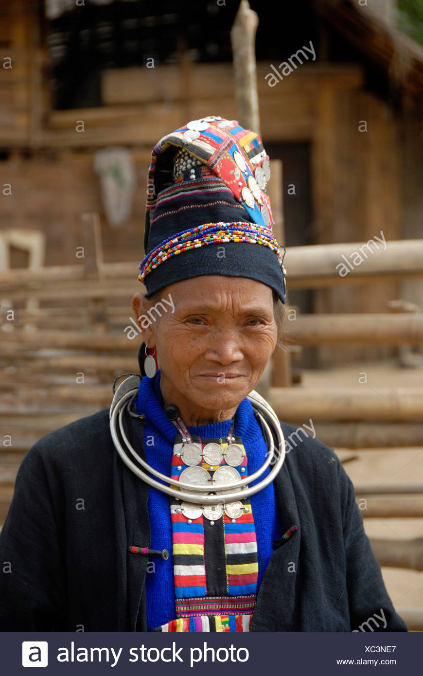 Portrait of old woman of the Akha Loma ethnic group, traditional black costume, colourfully embroidered, cap, silver neck ring Stock Photo