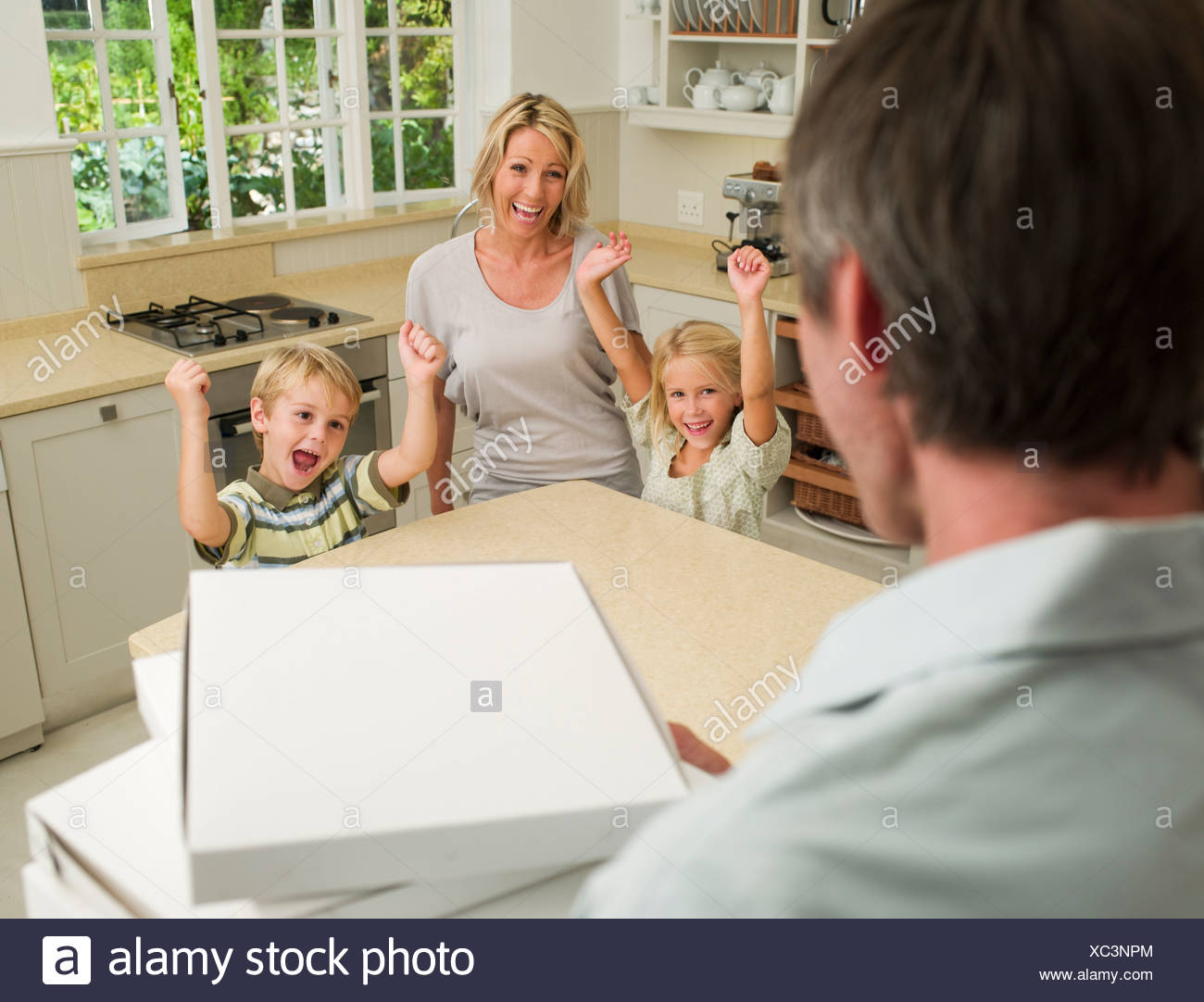 Man arriving in domestic kitchen with pizza boxes and family cheering - Stock Image