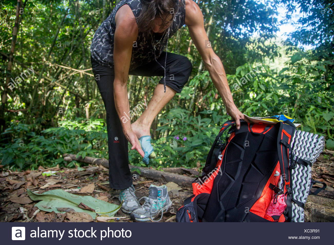An expedition member removes her shoes and socks to tend to bug bites and leeches. - Stock Image