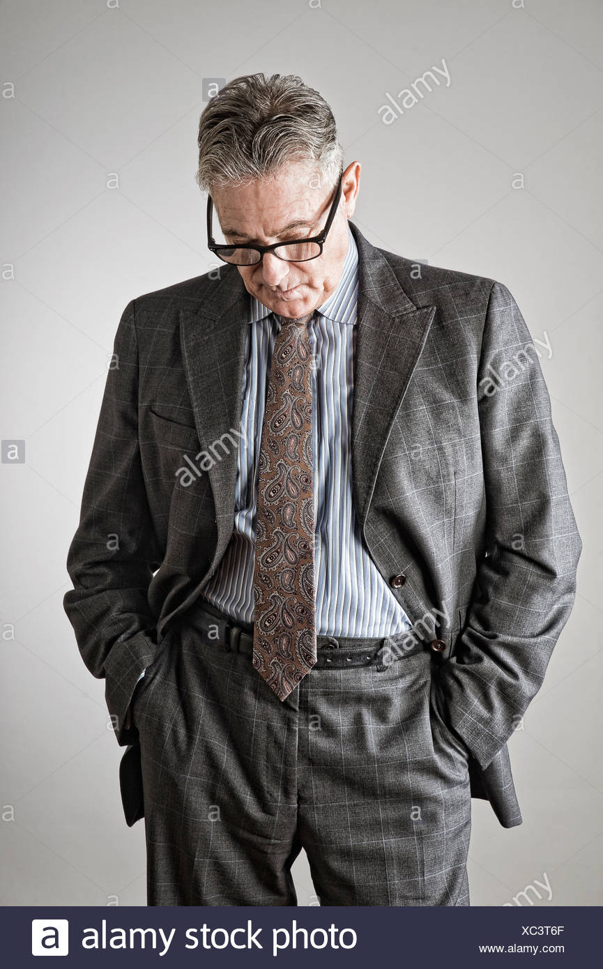 Senior man with hands in pockets, looking down - Stock Image