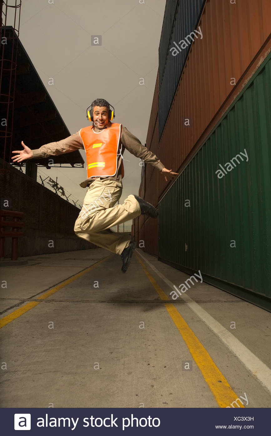 Dock worker wearing headphones and jumping at a commercial dock - Stock Image