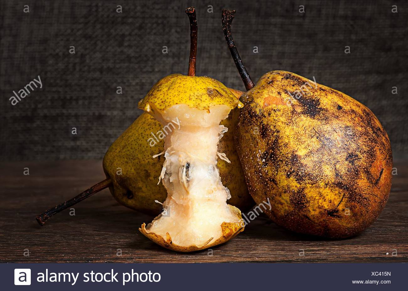 Two pears and stub standing on wooden table background sacking. - Stock Image