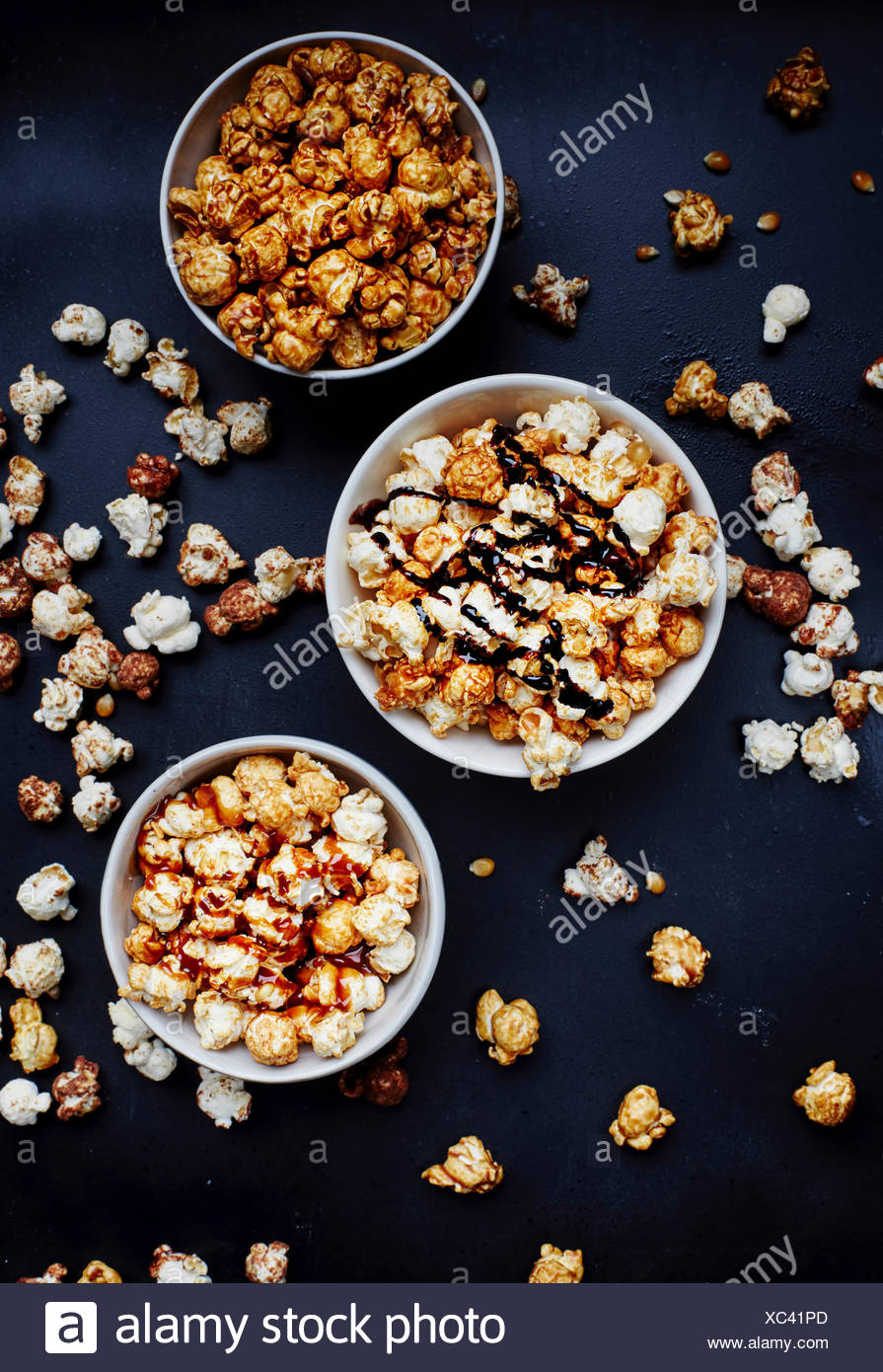 Three bowls of popcorn from above - Stock Image