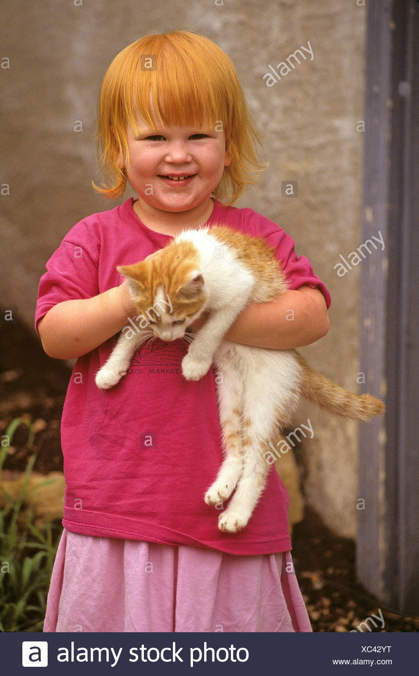 A baby girl and her kitten. - Stock Image