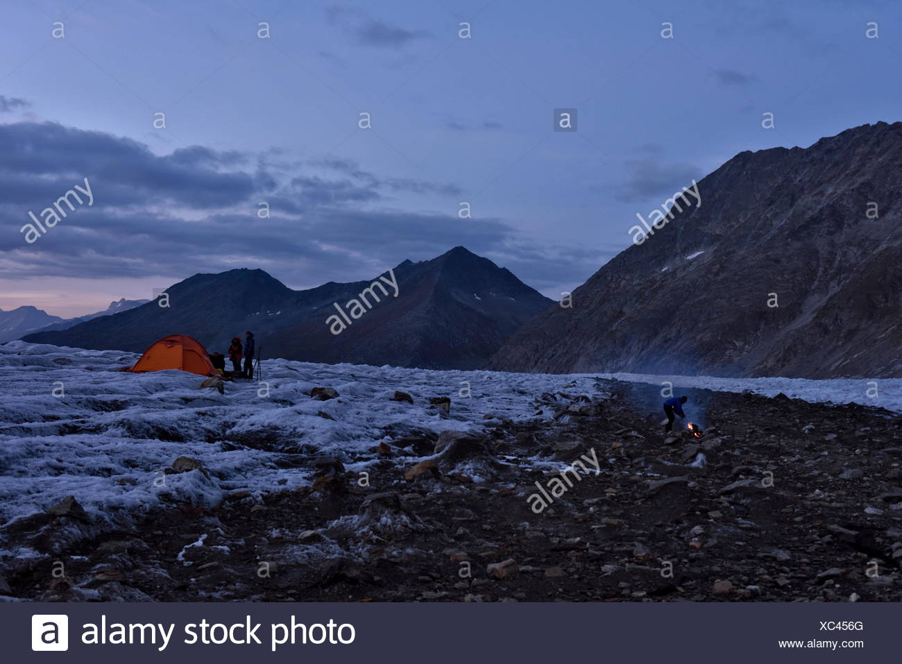 The team of Italian cave explorers settle into the evening at their base camp on the Aletschgletscher. Warm twilight illuminates the orange tents - Stock Image