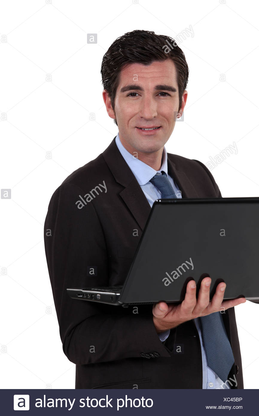 Executive with computer in hand - Stock Image