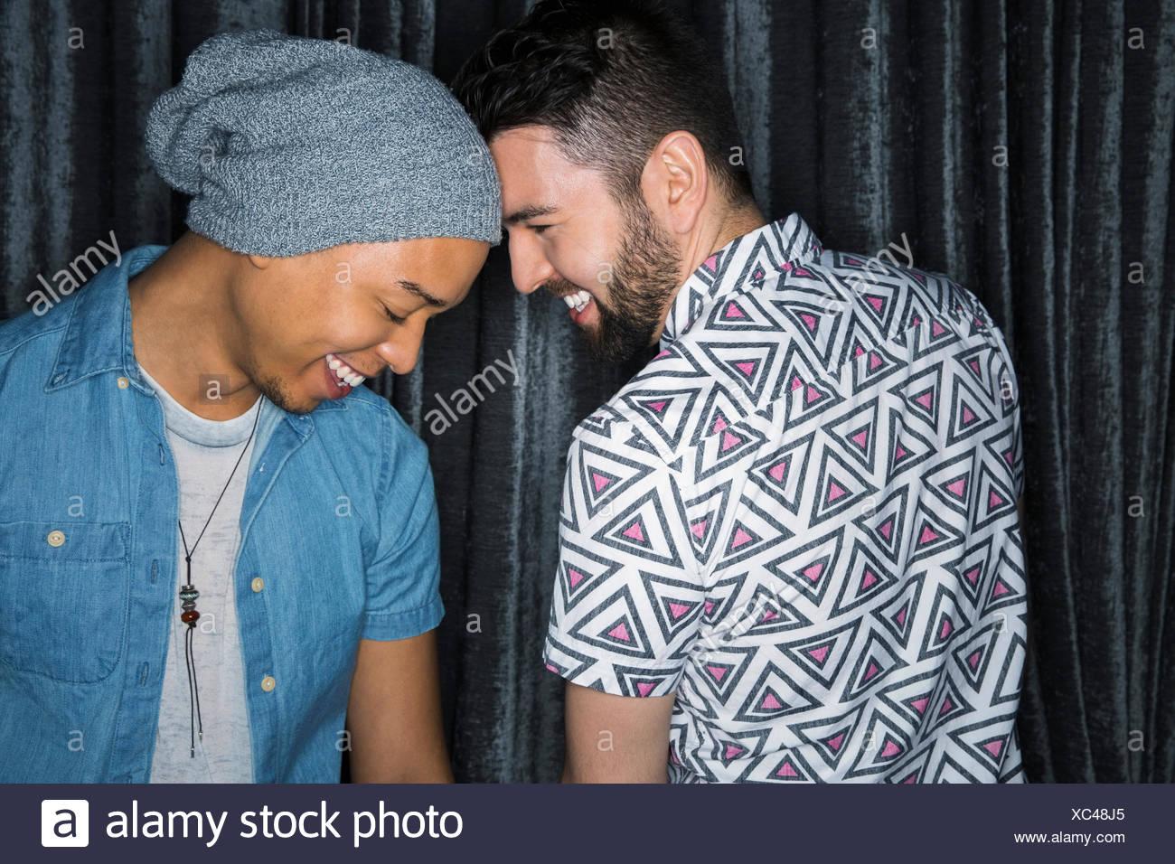 Homosexual men smiling head to head - Stock Image