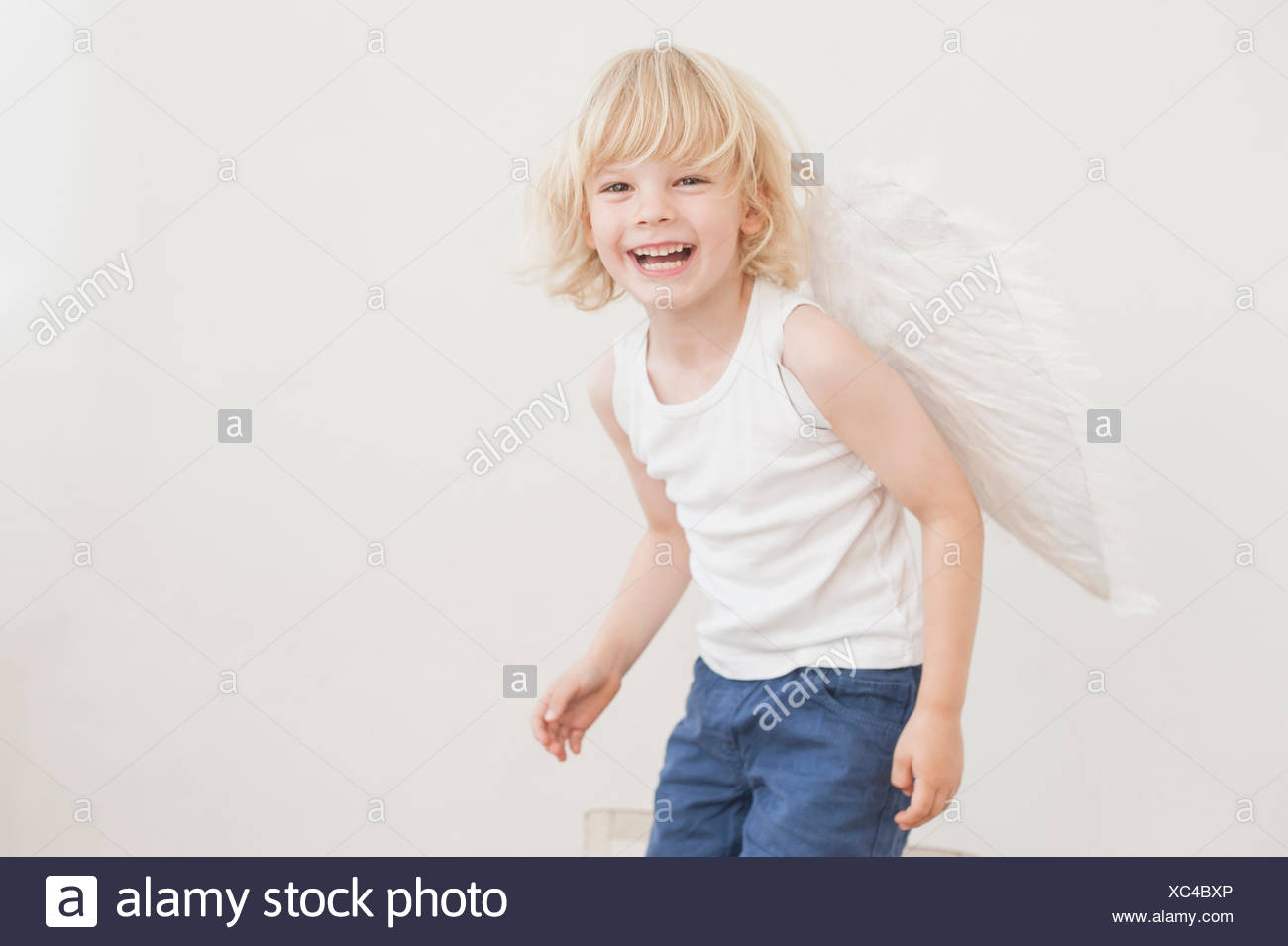 Portrait of laughing little boy with angle wings - Stock Image