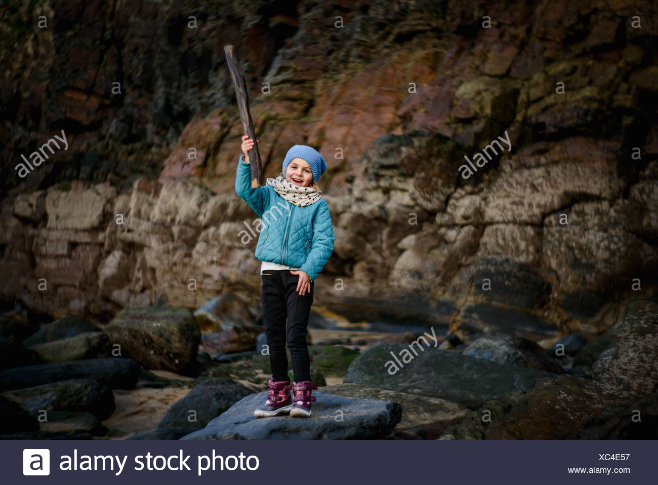 Girl standing on rock at the beach holding a stick - Stock Image