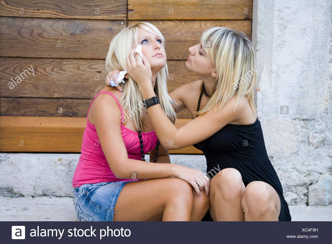Two young women together, one is crying - Stock Image