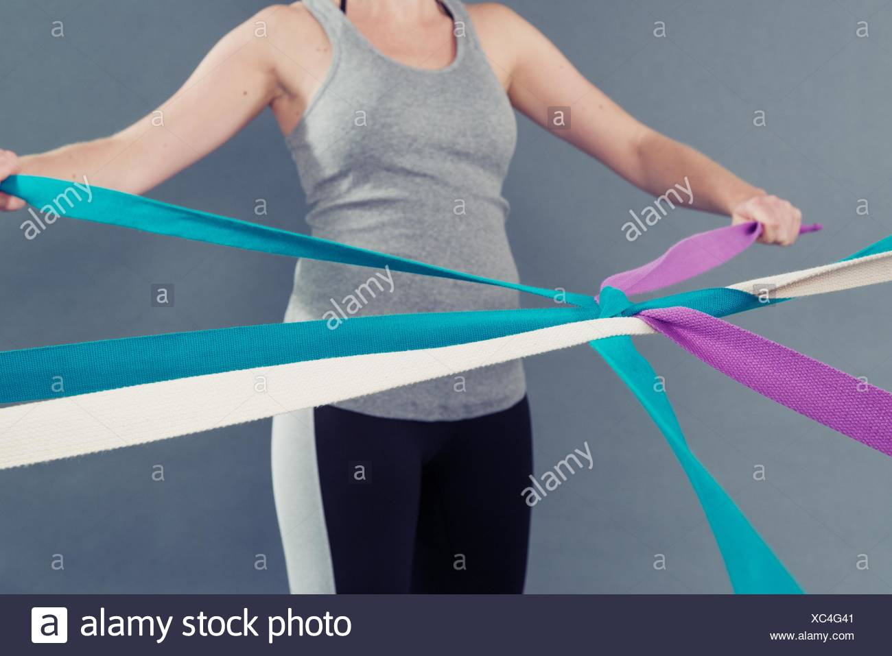 Young woman using coloured bands, grey background - Stock Image