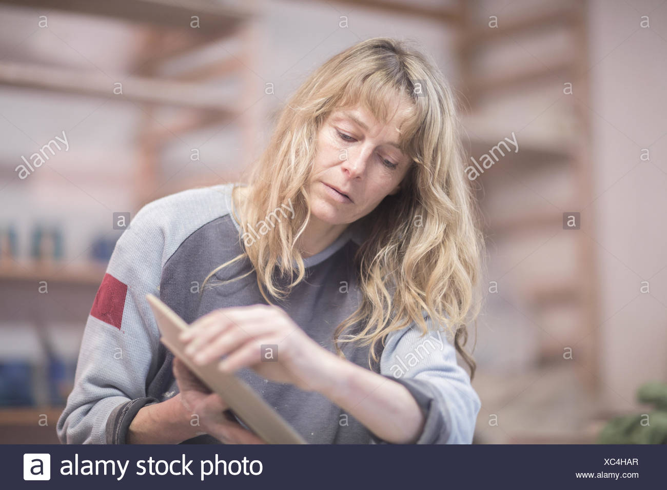 Female potter touching edge of plate in workshop - Stock Image