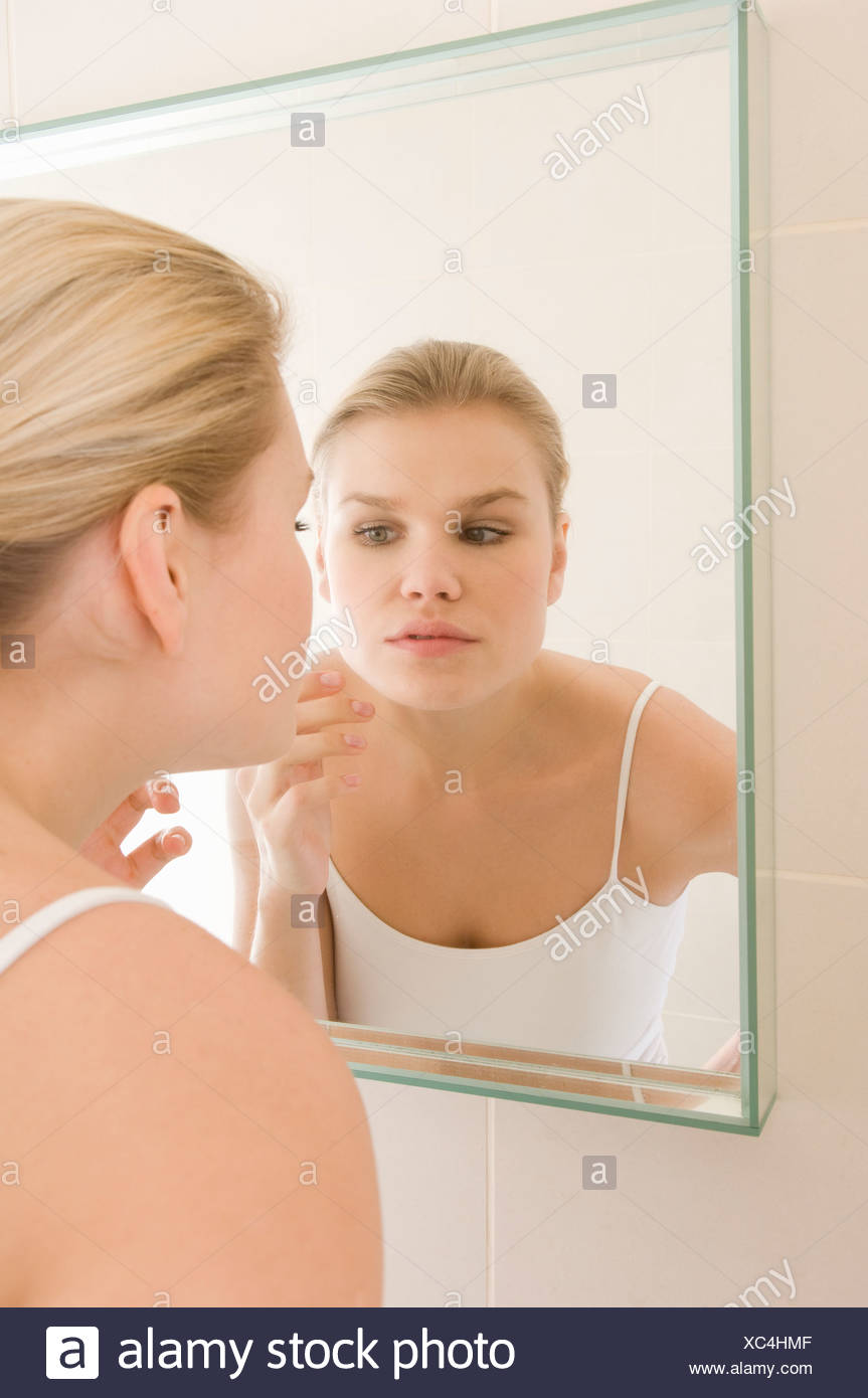 Female beauty inspecting skin in mirror - Stock Image