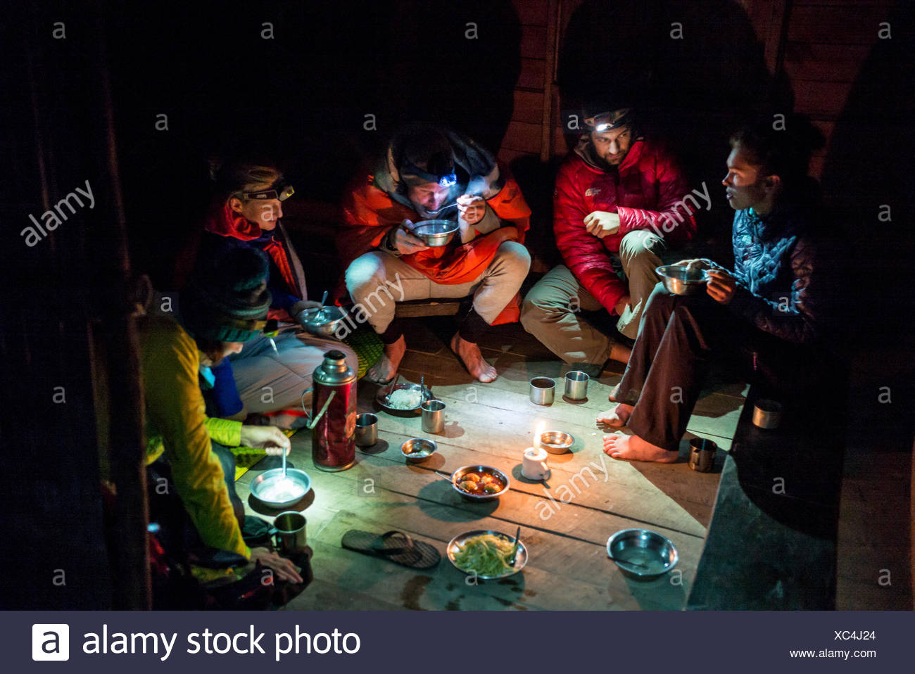 Expedition members share a nighttime meal. - Stock Image