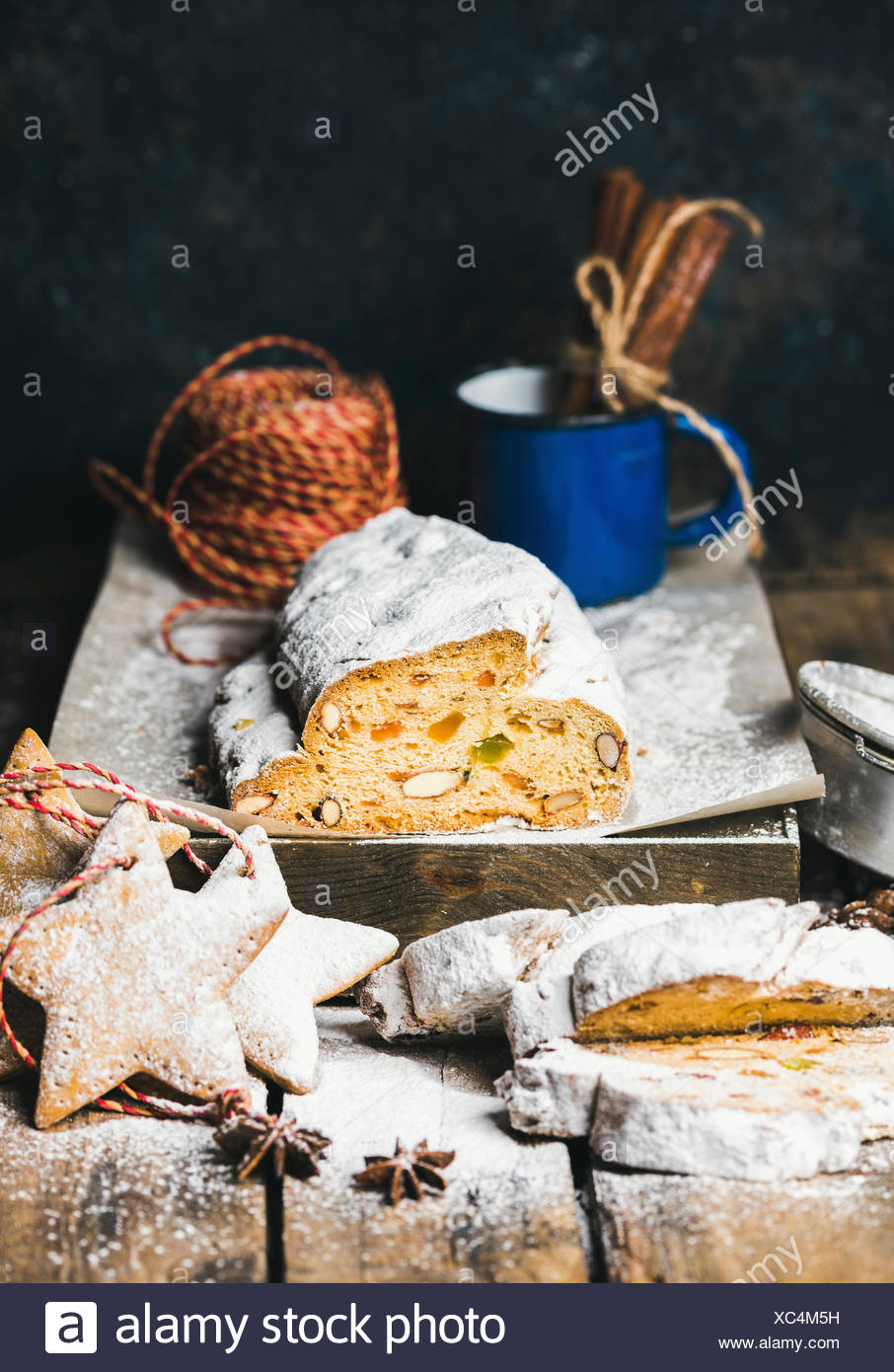 Traditional German Christmas cake Stollen with festive gingerbread cookies, selective focus, dark blue grunge background, copy space - Stock Image