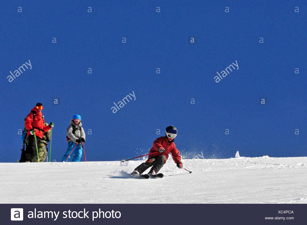 A young male skier skiing in the backcountry while his instructor looks on at Kirkwood Mountain Resort, CA. - Stock Image