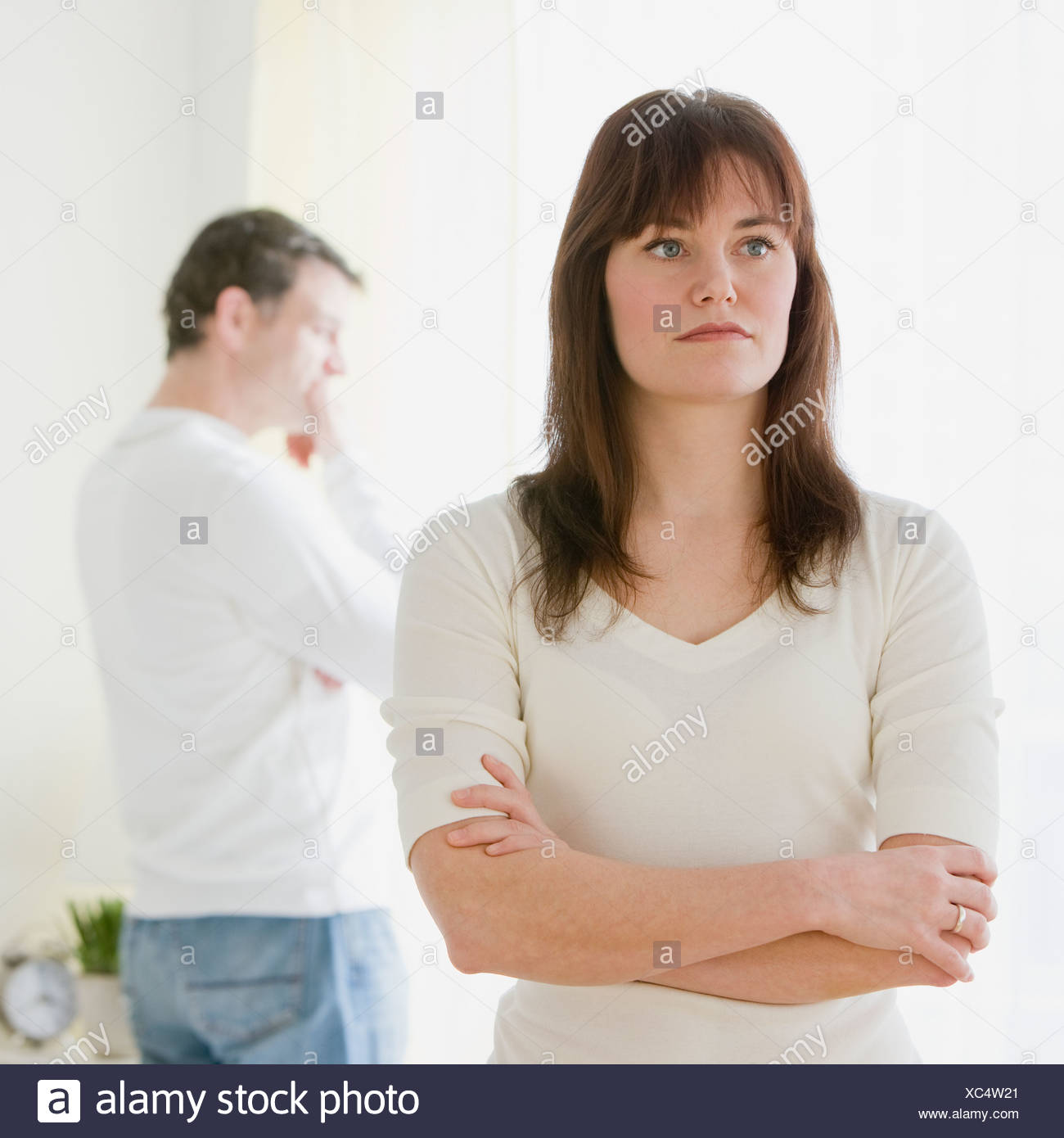 Woman with arms crossed and husband in background - Stock Image