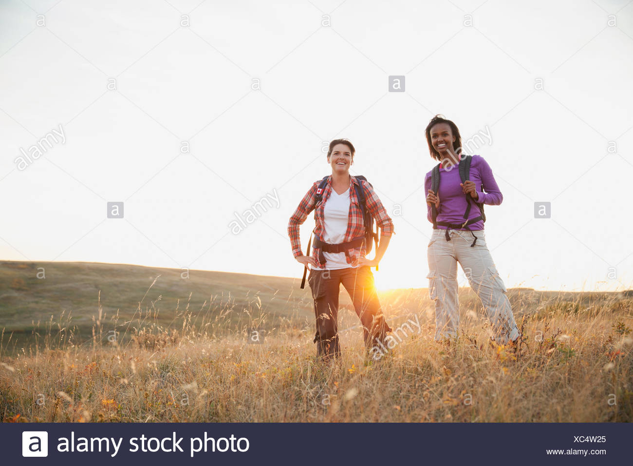 Two women standing in field at dusk. - Stock Image