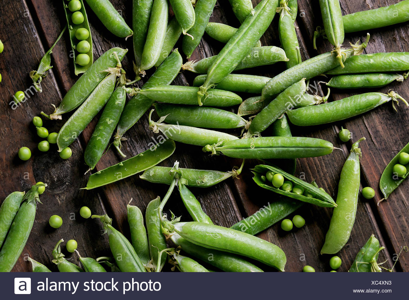 Young organic green pea pods and peas over old dark wooden planks background. Top view with space. Harvest, healthy eating. - Stock Image