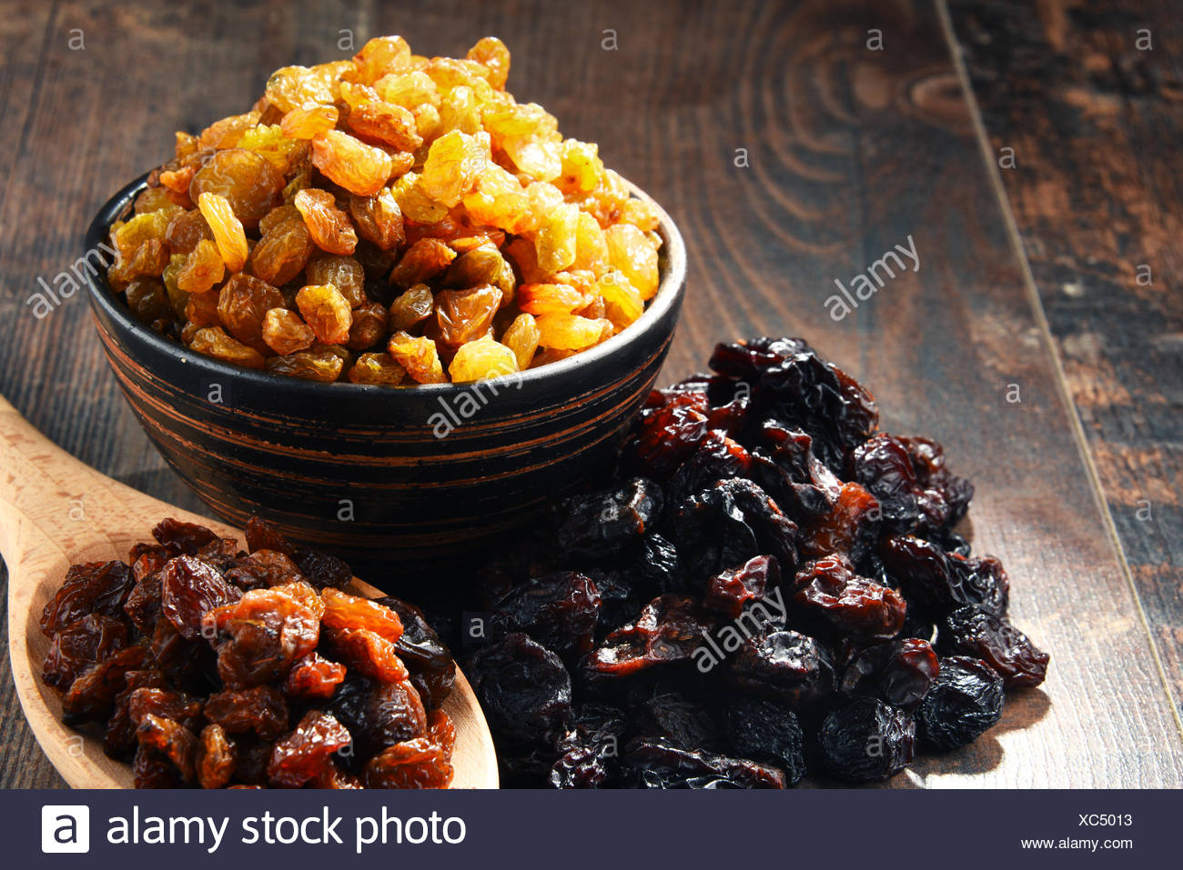 Composition with bowl of raisins on wooden table - Stock Image