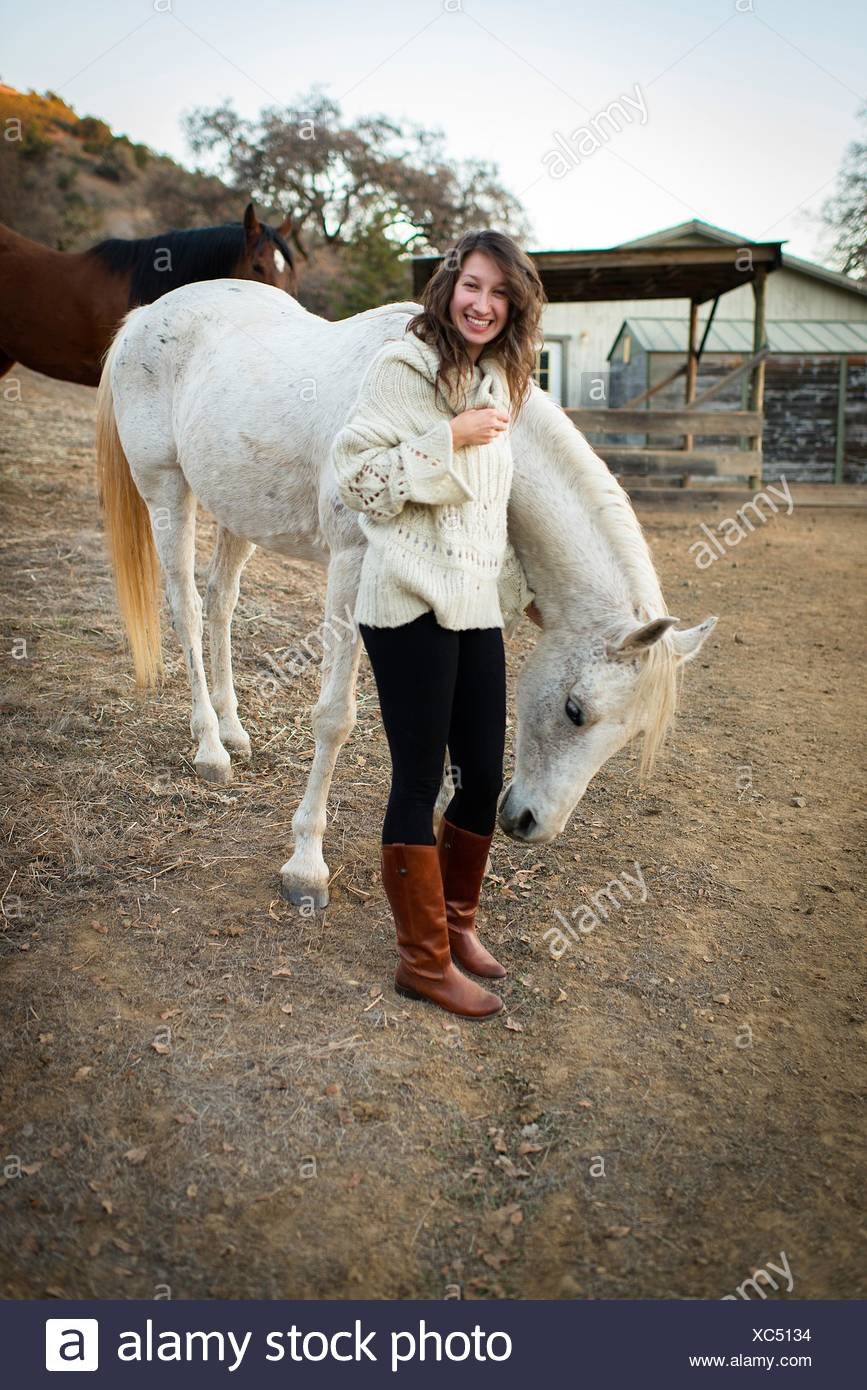 Portrait of young woman petting white horse - Stock Image