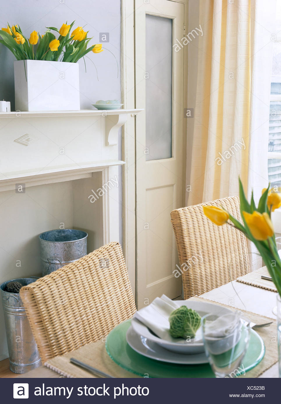 Wicker Back Chairs At Table With White And Green Crockery In An