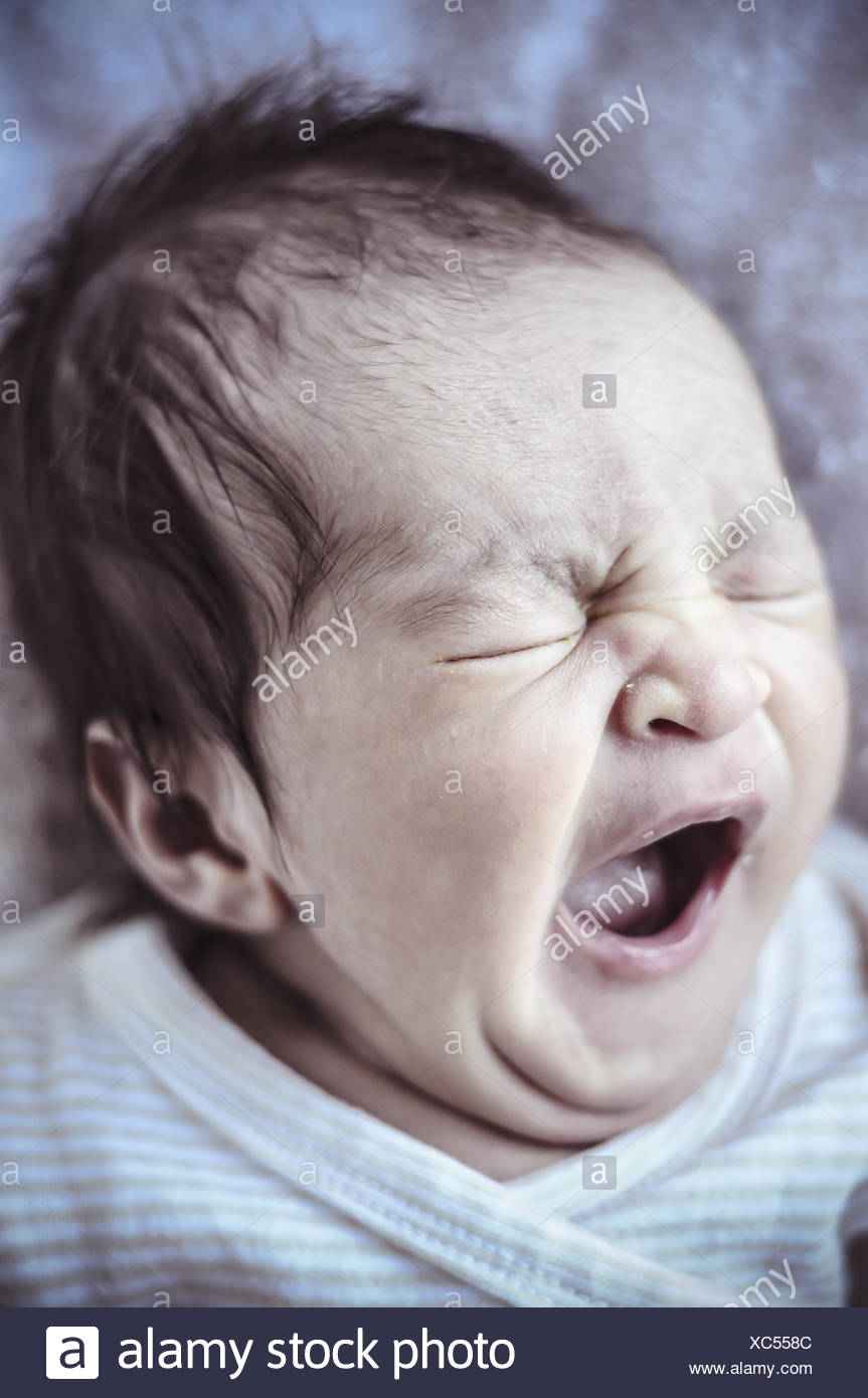 Yawn, new born baby curled up sleeping on a blanket, multiple expressions - Stock Image