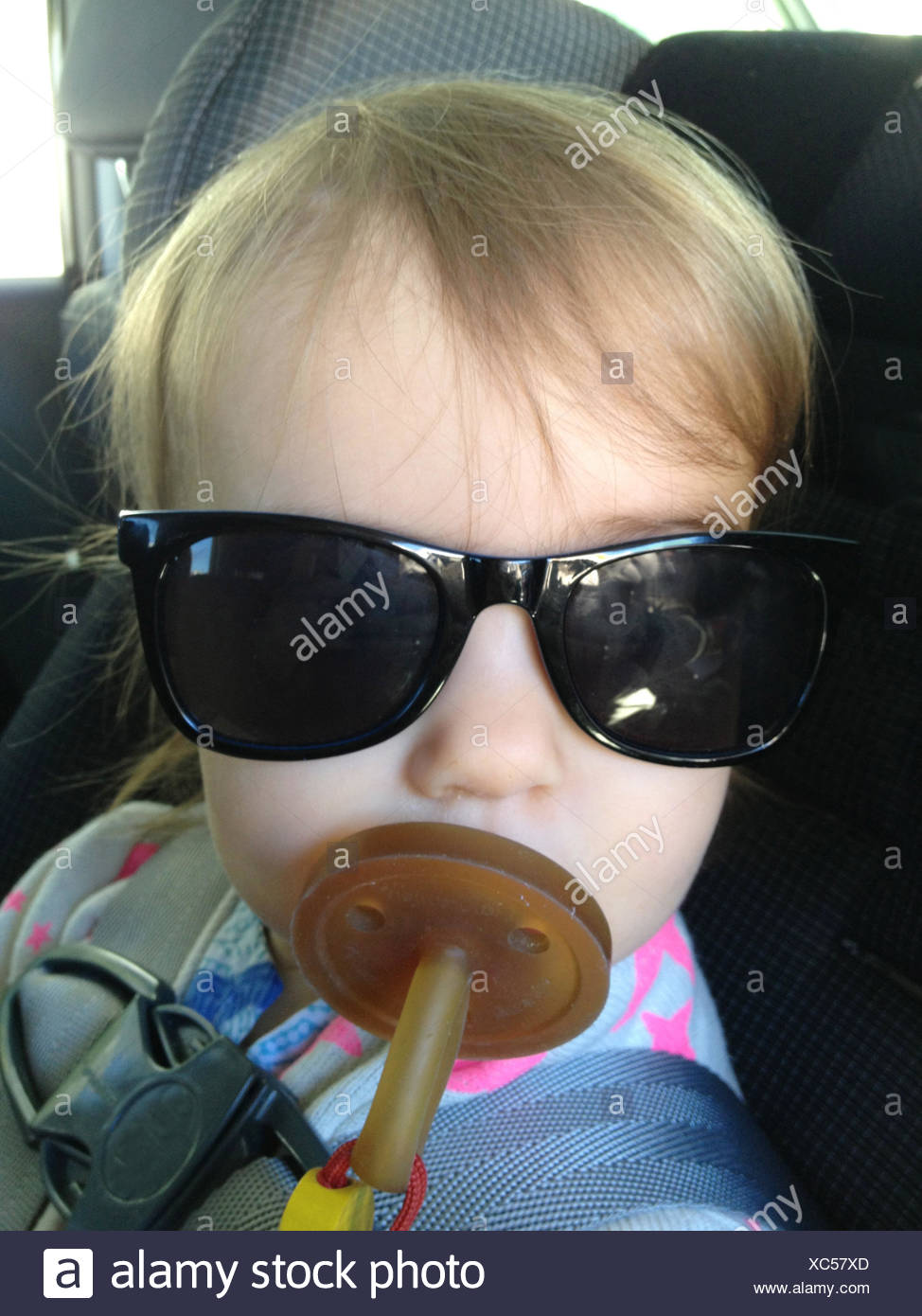Portrait of girl (18-23 months) with dummy and sunglasses - Stock Image