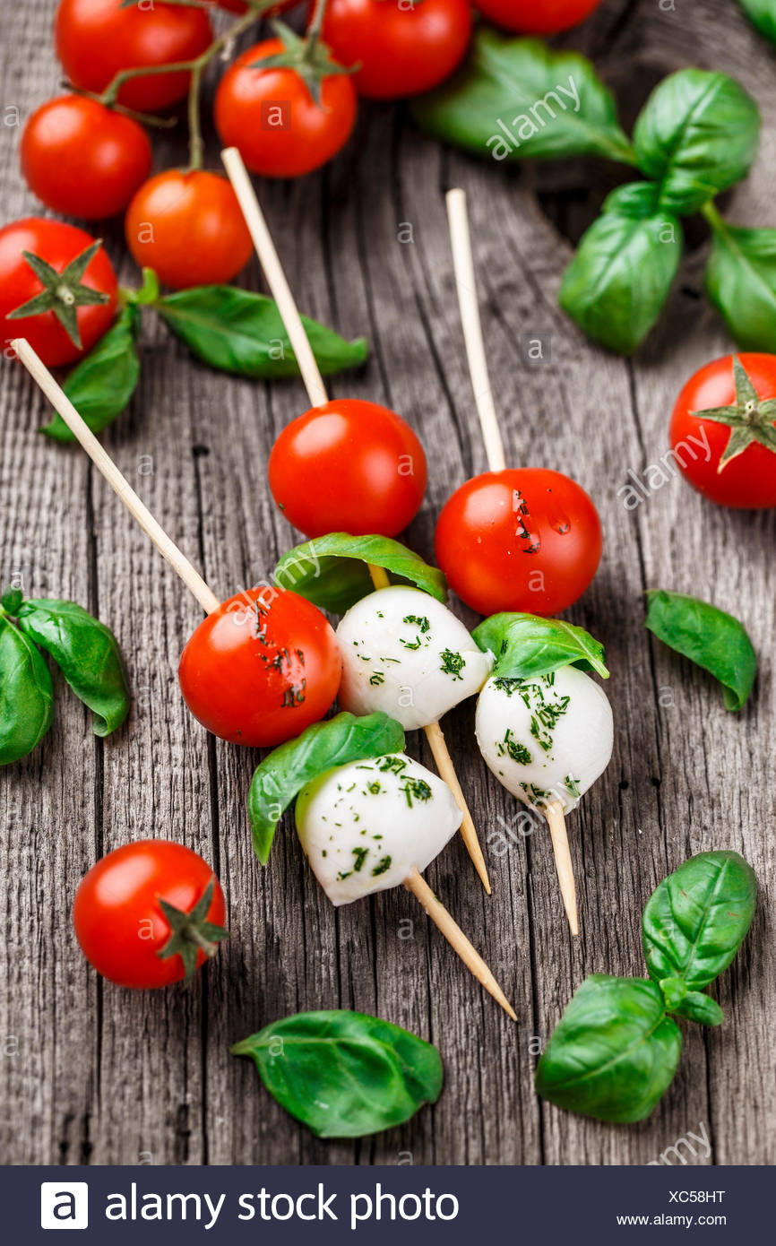 Skewers with tomato, basil and mozarella on a rustic background - Stock Image