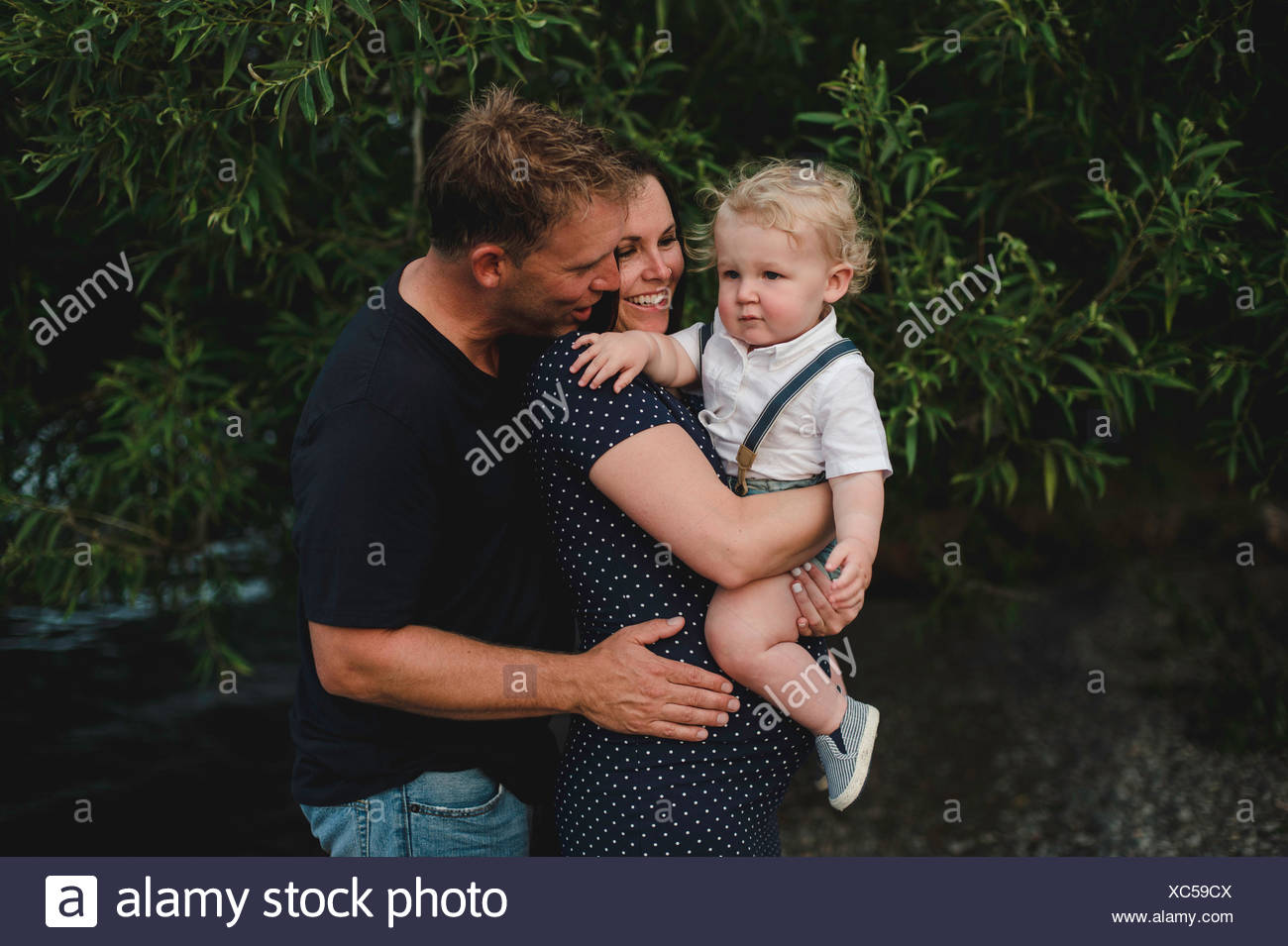 Pregnant couple carrying toddler son - Stock Image